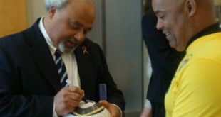 "Ambassador Eric Goosby, M.D., PEPFAR Coordinator, signs the 2010 World Cup Match Ball ""The Jabulani"" that was awarded to the Republic of Angola at the Brookings Institution in Washington, DC, as Victor Mooney, executive director of South African Arts International looks on."