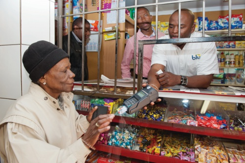 South African woman makes a purchase with her SASSA MasterCard Debit card at a local shop