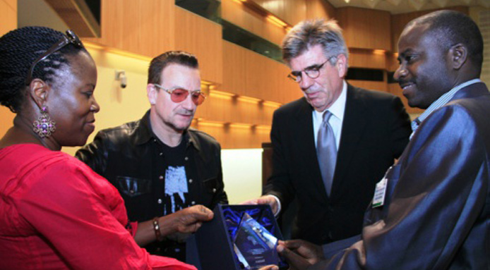 ONE's Dr. Sipho S. Moyo and Tom Freston hand over the ONE Africa Award trophy to ANSAF's Audax Rukonge as Bono watches
