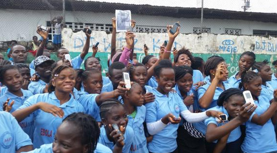Liberian youths flash their mobile phones in support of UNICEF's U-Report (UNICEF Liberia)