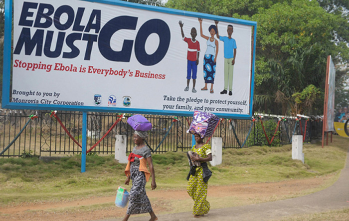 """Two women in Monrovia, Liberia, walk in front of a billboard, which says """"Ebola must go. Stopping Ebola is Everybody's Business."""" Photo: UNMIL/Emmanuel Tobey"""